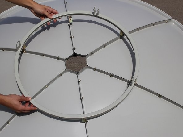 Image 1/1: Set the pipe ring in the metal brackets circling the center of the dish.