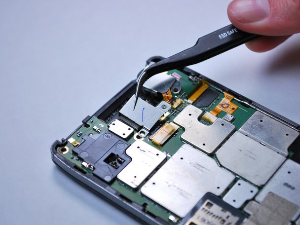 Using tweezers, remove the back facing camera cover.