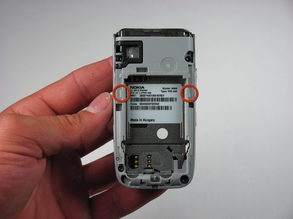 Image 1/1: The picture to the left shows the location of the plastic tabs that attach to the upper cover of the phone.