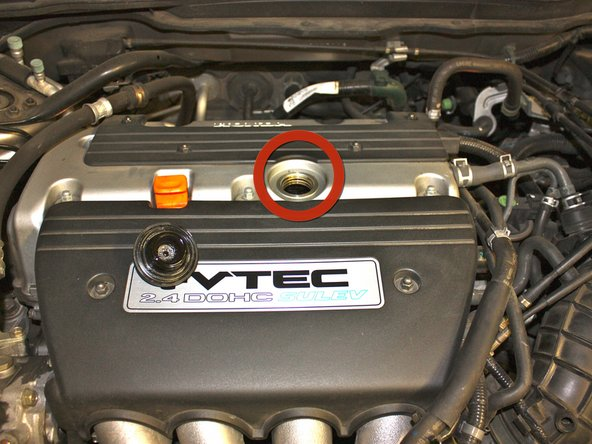 Locate the oil fill cap on top of the engine and unscrew it.