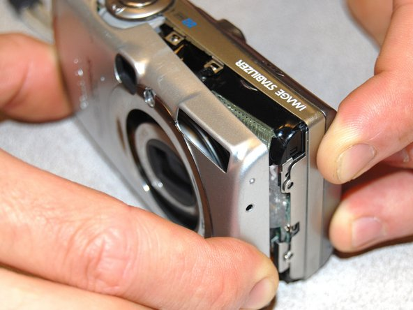 Image 3/3: Remove the front face by gently peeling the housing away from the camera.
