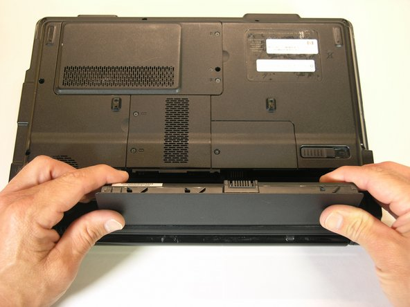 Pull the battery up and towards you to remove it from the laptop chassis.