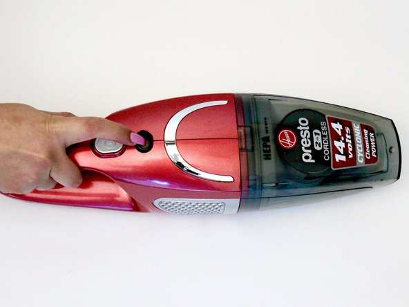 Press the hand vacuum's gray release button located directly below the power button to release the dust container from the hand vacuum.