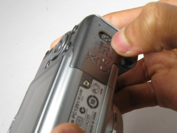 On the bottom of the camera, use your thumb and push the battery lock up to open.  The battery compartment door should then spring open and batteries will slide out.