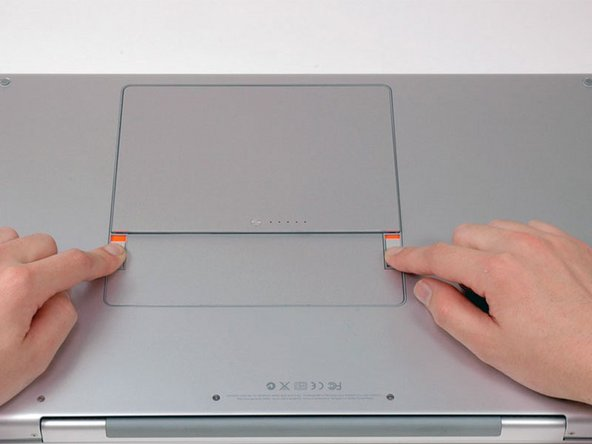 Use your fingers to push both battery release tabs away from the battery and lift the battery out of the computer.