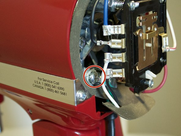 Using a Phillips #2 screwdriver, remove the 12mm screw by holding the grounding wire in place and rotating it counterclockwise.