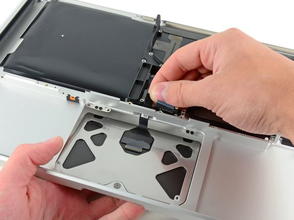 Carefully dislodge the edge of the trackpad closest to the keyboard from its recess in the upper case by pushing it away from the brackets attached to the upper case.
