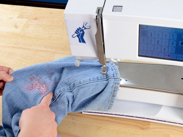 Slide the pant leg off the arm of the sewing machine.