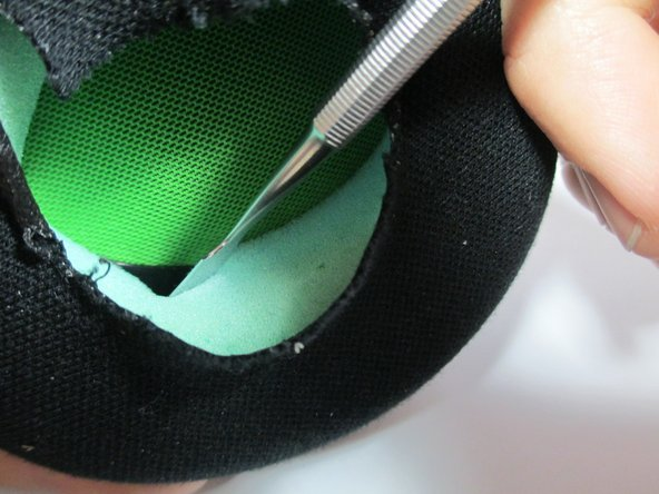 Insert the metal spudger between the foam ear pad and the black plastic speaker cover.