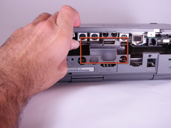 Place your hands on the lower case, just above the I/O panel, and slowly lift the lower case a few inches above the main body of the computer.