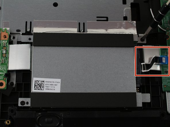 Disconnect the hard drive ribbon cable from the mother board as shown by lifting the release tab and gently pulling the cable away from the socket.