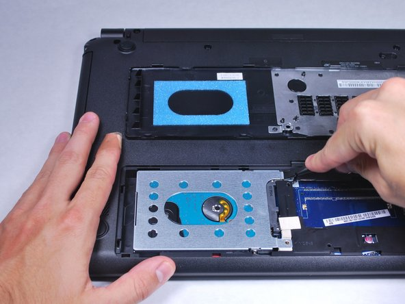 Use a nylon spudger to slightly pry up the hard drive near the screw holes.