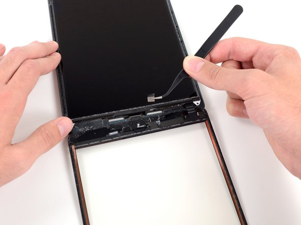 Image 2/2: Use a pair of tweezers to peel up the small piece of tape connecting the LCD frame to the right speaker.