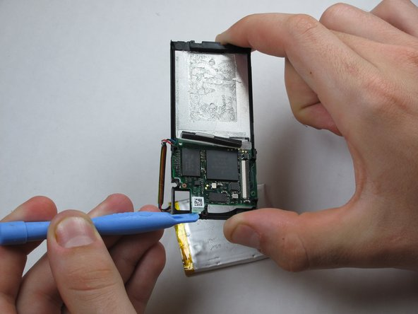 Pry up the memory board from center piece with a Zune opening tool and gently pull it off.