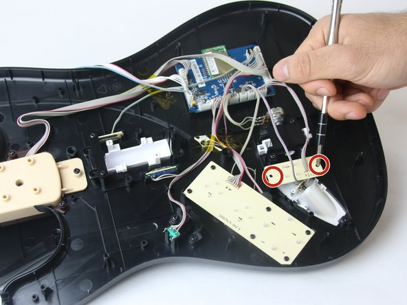 Using a size J1 philips head screwdriver, remove the two black 5 mm screws (circled in red) from the back of the power button component. You can identify this by the code J5-B on the component.