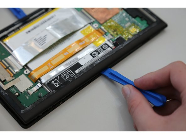 Carefully run the plastic opening tool along all the edges of the tablet.