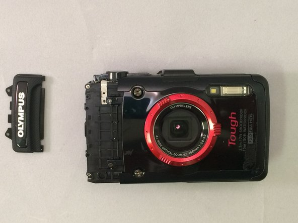Using a plastic opening tool, gently pry the Olympus grip up and remove it.