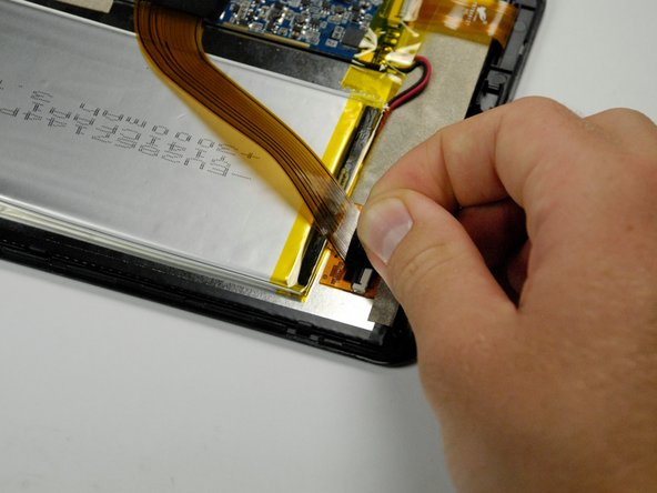 Remove the black tape covering the zero insertion force (ZIF) connector that holds down the end of the yellow colored ribbon wire that lies across the battery.