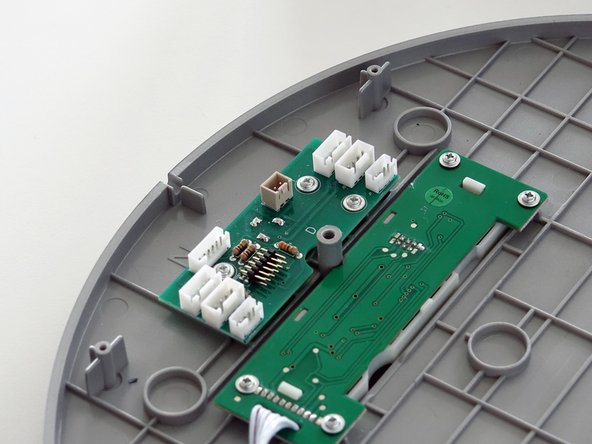 Remove the dock sensor from the circuit board. Grip the small white tab on the side and pull up.