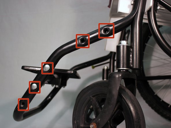 Image 2/2: Make sure the two bolt holes on the footrest bar line up with two of the holes on the front frame
