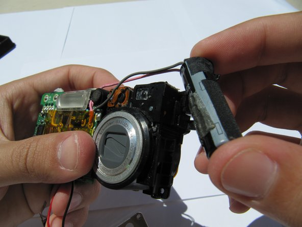 Hold the camera firmly and gently remove the capacitor (attached by adhesive) by wiggling it loose.