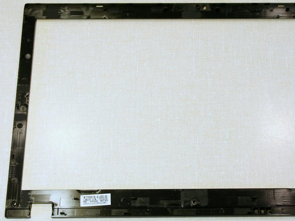 Starting from the bottom of the screen, release the plastic clips holding the bezel by pushing horizontally inward and prying upward with a spudger.