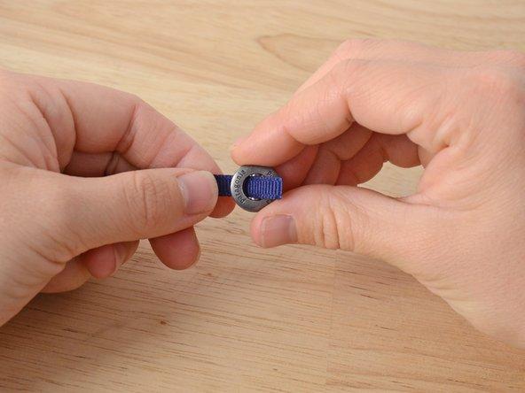 Das Band von hinten durch den Knopf fädeln, über den Steg und durch das zweite Loch zurück.
