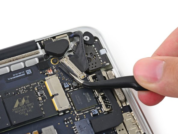 Grab the black plastic tab to flip the display cable connector open and pull it straight out of its socket on the logic board.