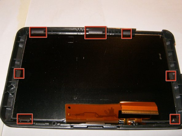 The LCD assembly is held in the front bezel by seven plastic tabs.