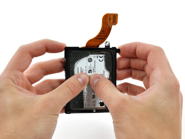 Use your thumbs to push the hard drive away from its bracket.
