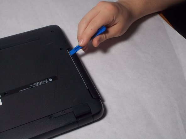 Remove the disk tray assembly by sliding it out from the side using the blue plastic opening tool.