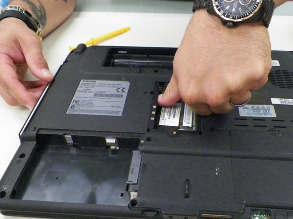 Push down metal rod until optical drive pops out from its container on the side of the device.