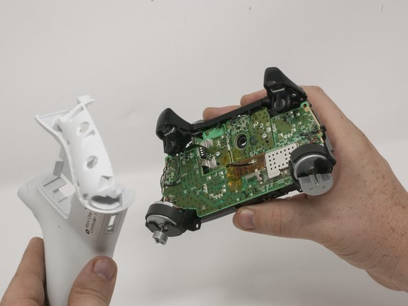 Turn the controller face down and gently lift the rear plate.