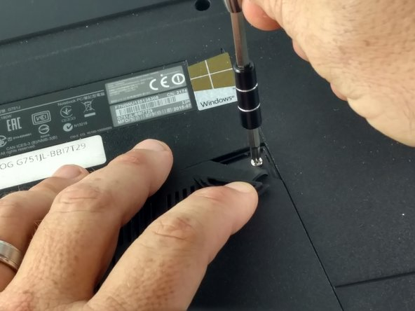 Image 2/2: Remove screw with a Phillips screwdriver.