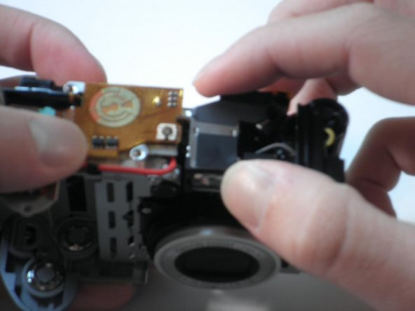 After removing the three screws, the only thing still holding the viewfinder in place is a small plastic peg.