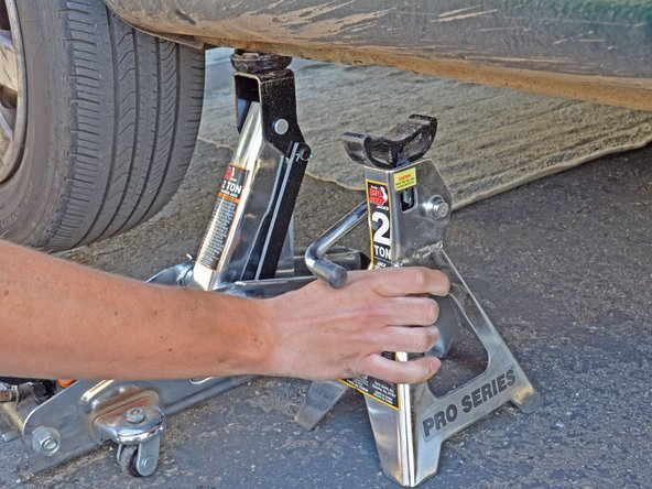 Use the handle on the jack stand to lower it and remove the jack stand from underneath the car.