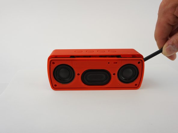 Insert the Spudger between the corners of base and the face of the speaker to open the device. The screw on the upper right corner may be difficult to take out. If you cannot take it out with a screwdriver, using force to pull the face of the speaker apart may break the plastic that surrounds the screw.