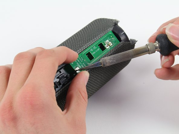Using a soldering iron, solder the two ends of the green Bluetooth adapter.