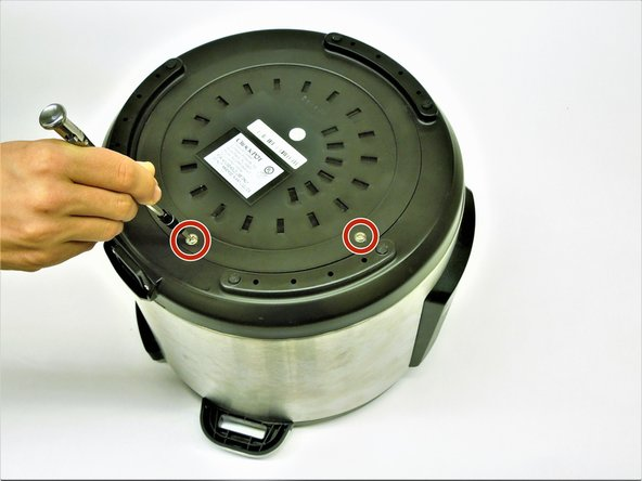 Carefully rotate the Crock-Pot so that the bottom is facing upward, allowing access to the electrical panel.