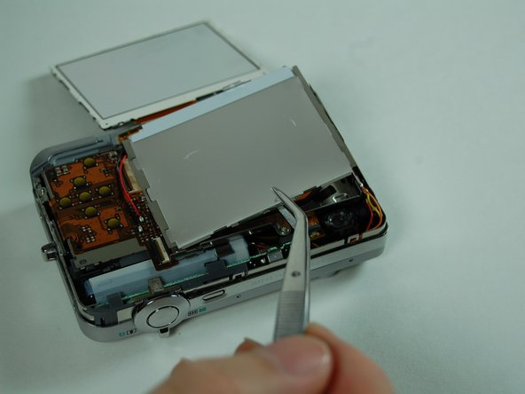 Under the LCD screen you will see an LCD casing. You will want to GENTLY pry this off using the tweezers.