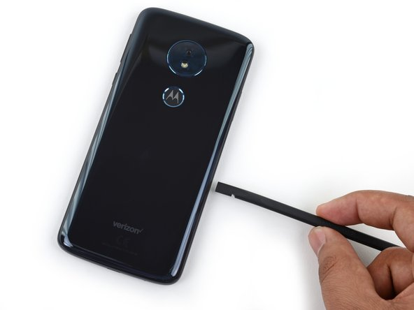 Insert the flat end of a spudger into the lower half of the right side of the phone about 2 cm and slide it down the right edge to release the right strip of adhesive.