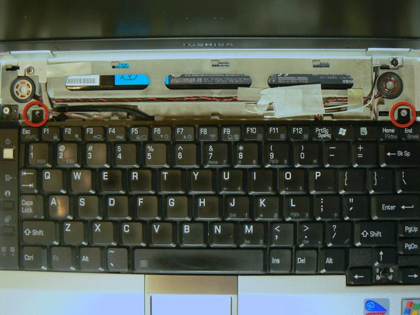 Use a Phillips head #00 screwdriver to remove the two silver screws at the top of the keyboard.