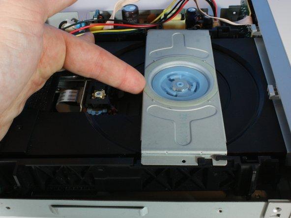 Image 1/2: Sliding the disc tray bracket forward.