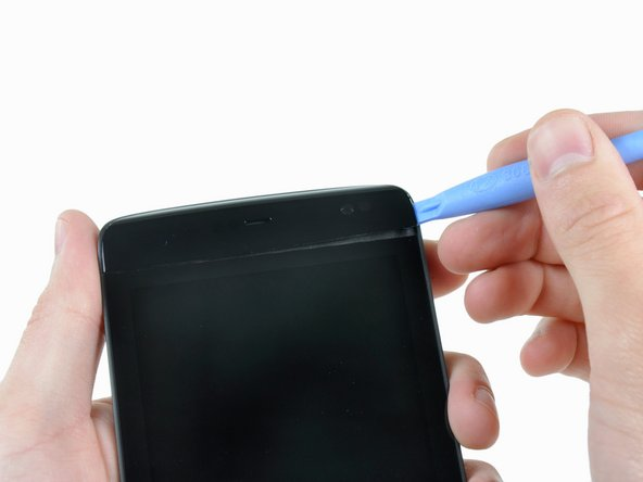 Image 1/2: A plastic opening tool is all that's needed to remove the bezel securely stuck to the top edge of the Streak.