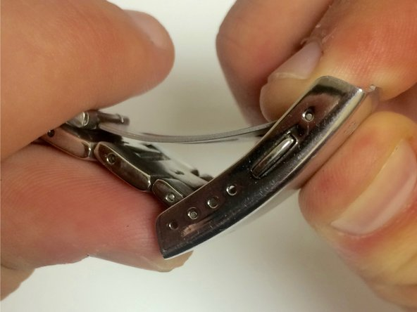 Squeeze the spring bar so it fits within the metal sides of the clasp.