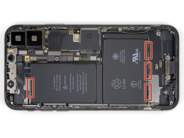 The iPhone X's battery is secured to the rear case by four pieces of stretch-release adhesive—one on the top cell, and three on the bottom.