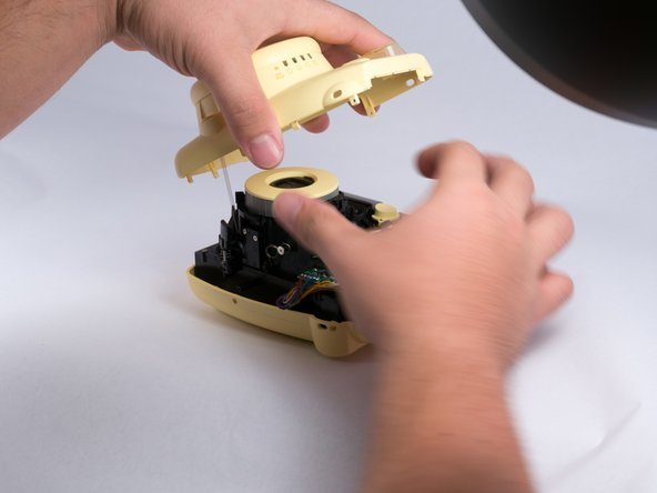 Once all screws are removed, gently pry open the front casing with your hands or a prying tool. Do note that there will be a spring that attaches the front casing and the main circuit board, so take care as to not break the spring.