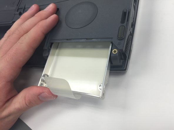 "Insert the new hard drive by pushing it into the compartment, leaving the new ""pull"" tab exposed."