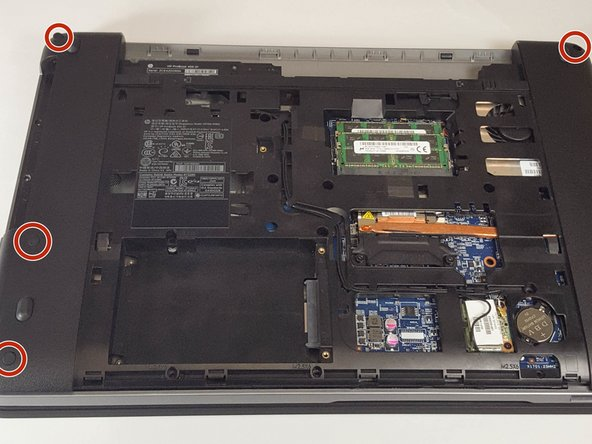 Use the tweezers to remove the six rubber stops on the side edges of the laptop.