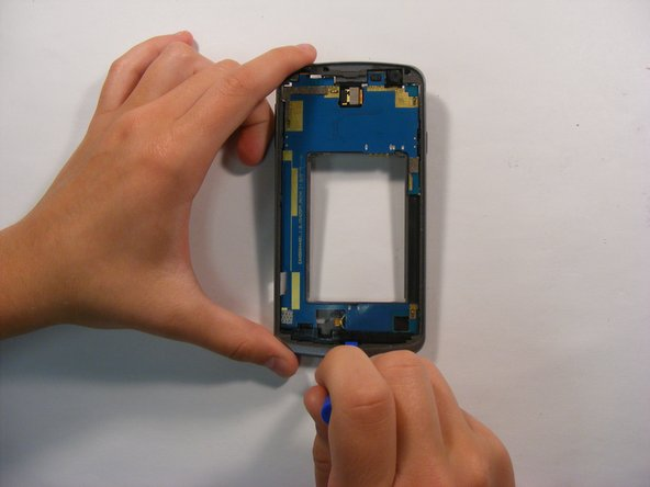 On the front side of the phone, push up on the plastic bottom shield using the plastic opening tool and remove it.